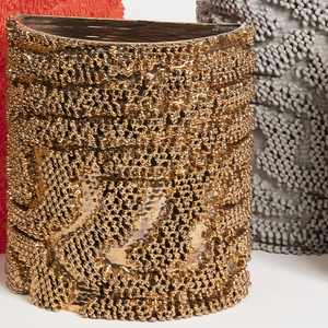 Five 3D-printed objects are cylinders that are flat on one side. The objects have an intricate textured surface resembling loops of yarn. The same texture is printed on each object, but the underlying material is different.