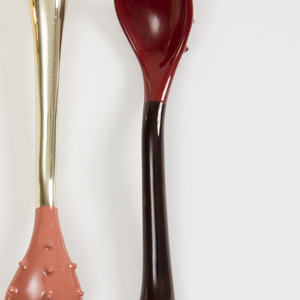 Small bumps sized 4mm cover the interior of a pink spoon that has a black handle.