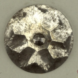 Button with ornament in design of flower with eight pointed petals; central boss; steel shank.  On card 59