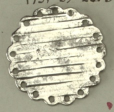 Flat button ornamented with parallel ridges; edge cut in scallops with circular hole in each scallop. Steel shank.  On card 59