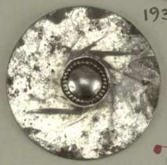 Flat button with design of swirled leaves around central boss. Steel shank.  On card 59