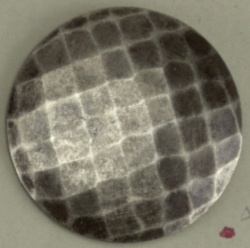 Slightly convex button ornamented in design of lines crossing diagonally; gun-metal finish; steel shank.  On card 59
