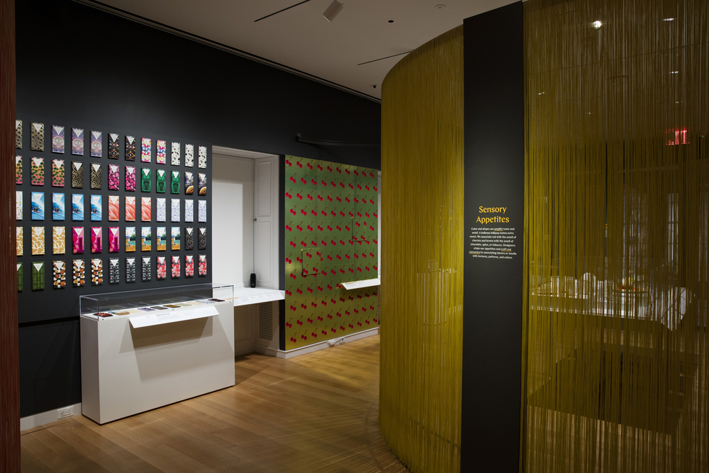 A gray metal text panel is mounted to the armature of a curved wall made of metal and yellow woven nylon fibers. Through the fibers, a partial view of a table with objects. On a dark gray wall at left are many colorful chocolate bar packages. In a case below are additional chocolate boxes and bars. At right, a wallpaper with rows of bright red cherries against a shiny gold ground.
