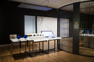 A long gray table contains some of the exhibition objects included in Shaping Sound: Sound Spheres, LABA Speakers, Ultrahaptics, and Vibeat. A wavy rectangular gray acoustic panel hangs from the ceiling above the table. A metal text panel is mounted to a curving wall at right made of metal and woven nylon fibers.