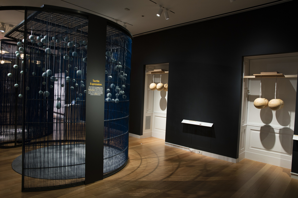 A gray metal text panel is mounted to the armature of a curved wall made of metal and blue woven nylon fibers. Through the fibers, a partial view of Snow Storm, an installation of blue woolen balls hanging from silver ribbons at various heights with a circular rug below. At right, view of two Tactile Headsets, each with four wooden spheres hanging from above.