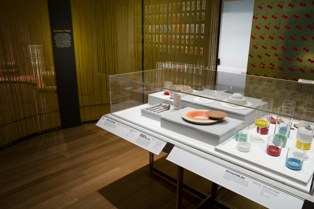 Within a large rectangular vitrine on a gray table are a number of pieces of sensory tableware including flatware, a pie plate, glassware, tumblers, and bowls. At left, a gray metal text panel is mounted to the armature of a curved wall made of metal and yellow woven nylon fibers.