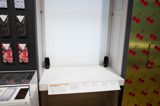A flat white surface with four white buttons is situated in the bay of a window. Two speakers are placed towards the back. Pushing the buttons plays music associated with sweet, bitter, salty, and sour tastes. In front of the buttons is a label rail.