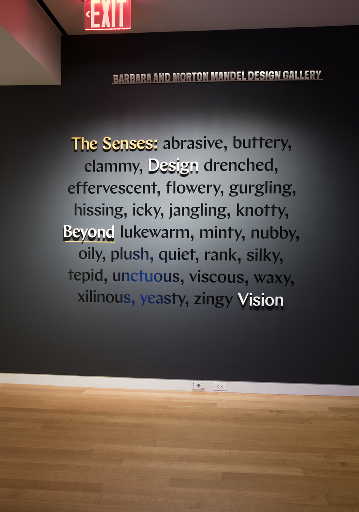 "The exhibition title ""The Senses: Design Beyond Vision"" appears in three-dimensional yellow and white letterforms against a dark gray wall at the entrance of Cooper Hewitt's Barbara and Morton Mandel Design Gallery. Mixed among the words are sensory adjectives arranged in alphabetical order in shiny black vinyl: abrasive, buttery, clammy, drenched, effervescent, flowery, gurgling, hissing, icky, jangling, knotty, lukewarm, minty, nubby, oily, plush, quiet, rank, silky, tepid, unctuous, viscous, waxy, xilinous, yeasty, zingy."