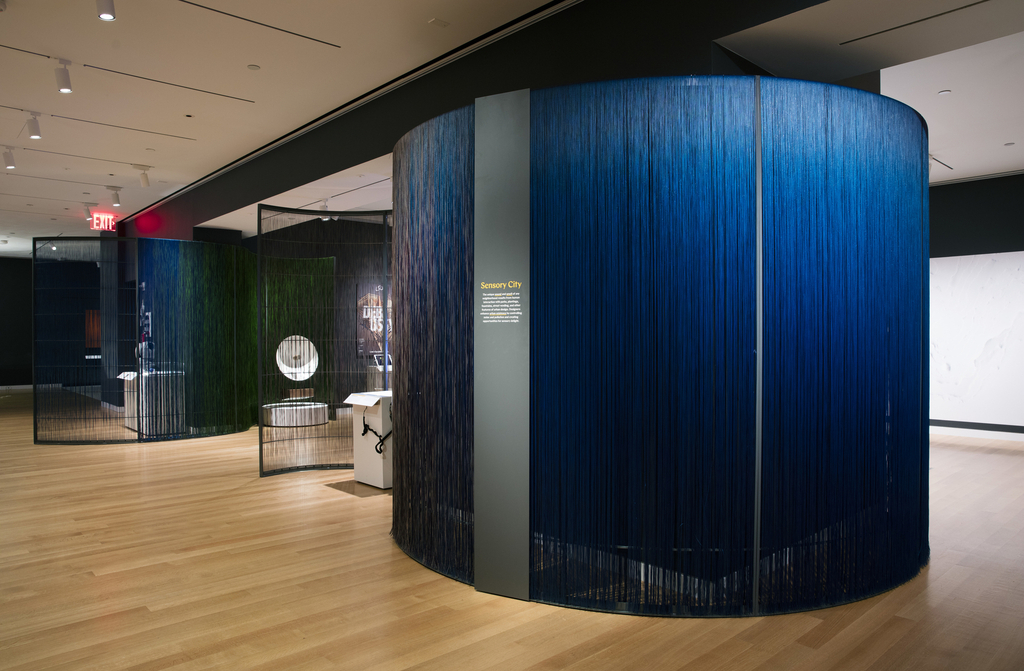 An open area of Cooper Hewitt's third floor gallery space is divided into sections by curving translucent walls made of blue and green nylon fibers. On the wall at center is a metal text panel mounted to the armature. Visible through the walls are pedestals with exhibition objects.