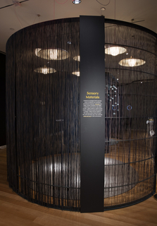 A gray metal text panel is mounted to the armature of a curved wall made of metal and dark woven nylon fibers. Through the fibers, a partial view of warm pendant light fixtures hanging from the ceiling.