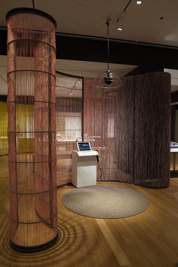 A white pedestal with an iPad, label rail, and SoundStik occupies an area of Cooper Hewitt's gallery space delineated by a curving wall made of pink and purple nylon fibers. Before the pedestal is a round gray wool carpet. Above, a clear sound dome hangs from the ceiling. Visitors standing on the carpet can hear the audio composition.