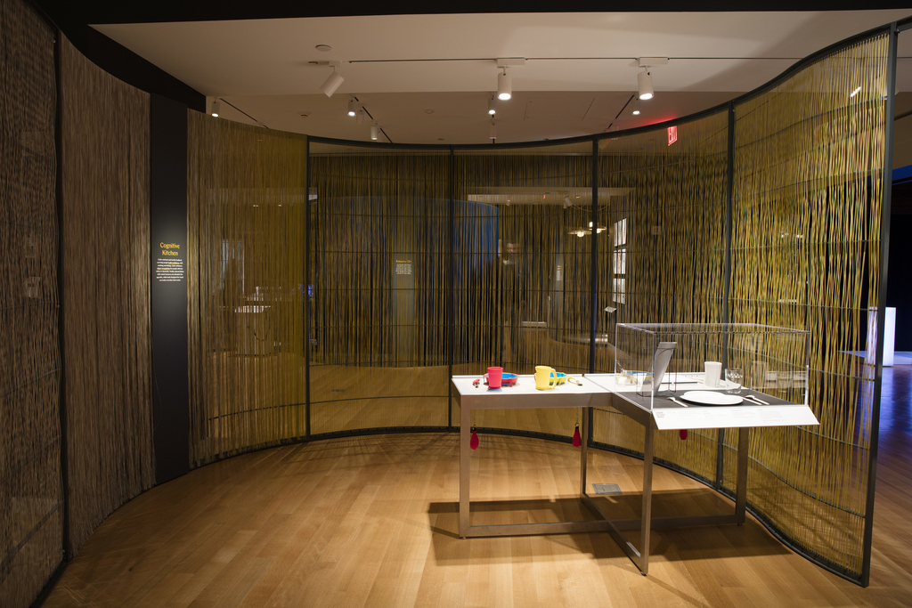 A table at right is filled with tableware. A jug, glass, plate, and cutlery are under a vitrine, while bowls, cups, a cutting board, mug, and hob guard are open for visitors to touch. The table occupies a space created by a curving wall with a metal armature filled with yellow woven nylon fibers. A gray metal text panel is attached to the wall's armature at left.