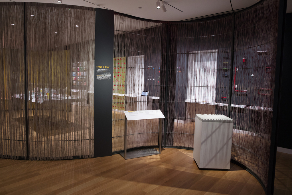 A curving wall divides an open gallery space. The wall has a metal frame and is filled with colorful woven nylon fibers. Dark gray gallery walls are partially visible through the fibers. At right, a rectangular pedestal is topped with a bumpy gray surface. A label rail stands to the left, and a metal text panel is mounted to the wall's armature beside it.