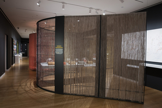 A curving wall divides an open gallery space. The wall has a metal frame and is filled with colorful woven nylon fibers. A gray metal text panel is mounted to the armature. Through the fibers, partial view of a table filled with objects.