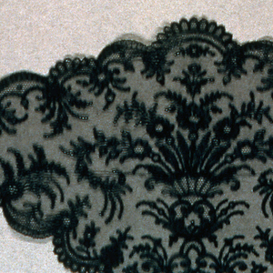 Woman's headcovering or fall cap in Chantilly-style black silk lace. With a large basket of flowers in the center and a deeply scalloped border all around with sprigs of flowers.