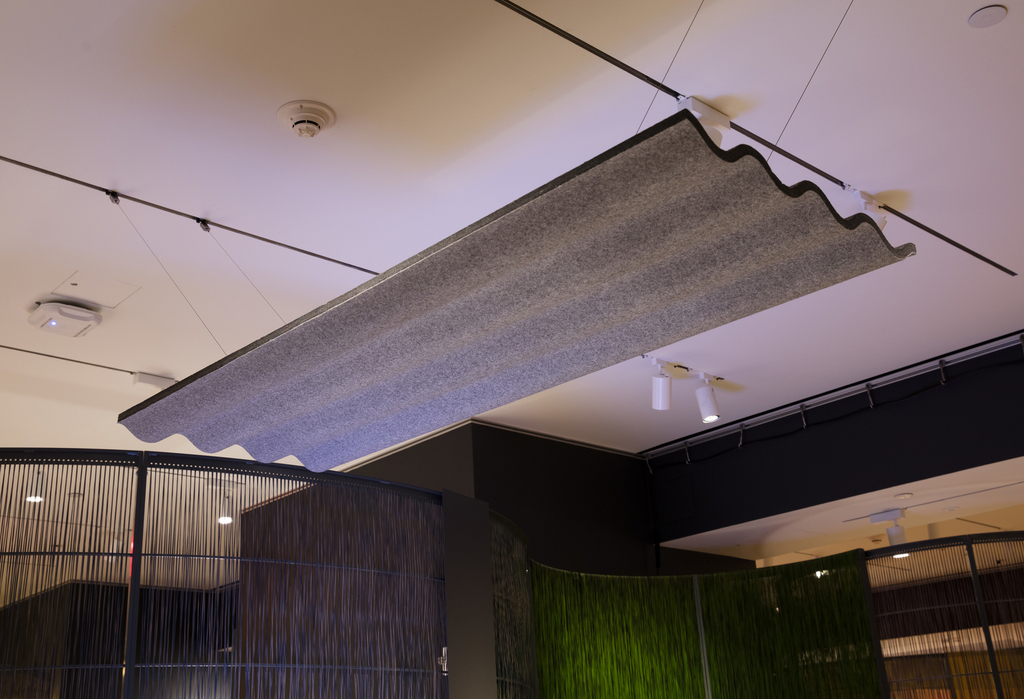 A plane of wavy material hangs from the ceiling over the table. It is made from gray compressed felt.