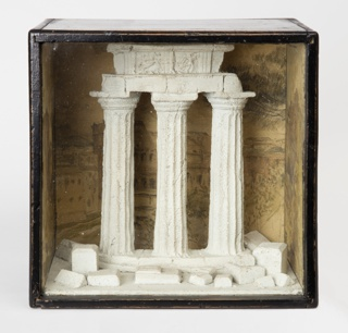 Nearly square wooden box with glass front containing a semicircular model of a classical temple ruin set before a painted scene of classical Roman ruins.