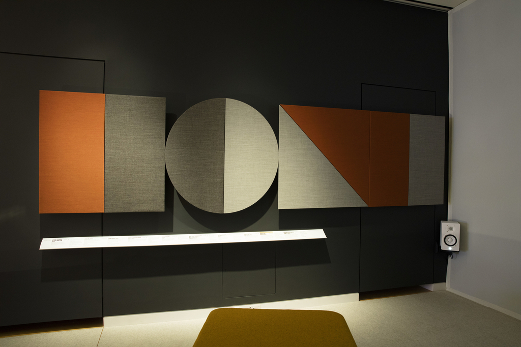 Round panels and square panels are wrapped in orange and gray wool fabric. Hanging on a dark wall of the Sensory Theater, these acoustic panels absorb waves of sound.