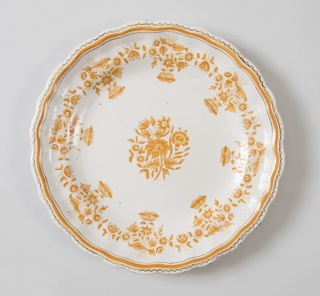 Circular form with shaped rim. Monochrome ochre decoration shows potato-flower at center and around edge.