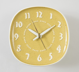 Clock with concave square ochre face with rounded corners; molded white numbers in graphic font;  hour and minute hand in white with second hand in black