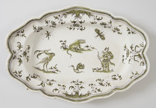 Oval platter with scalloped edges. Monochrome green decoration shows flora and fauna with a standing figure, dog, a plumed bird, and two flying insects at center.