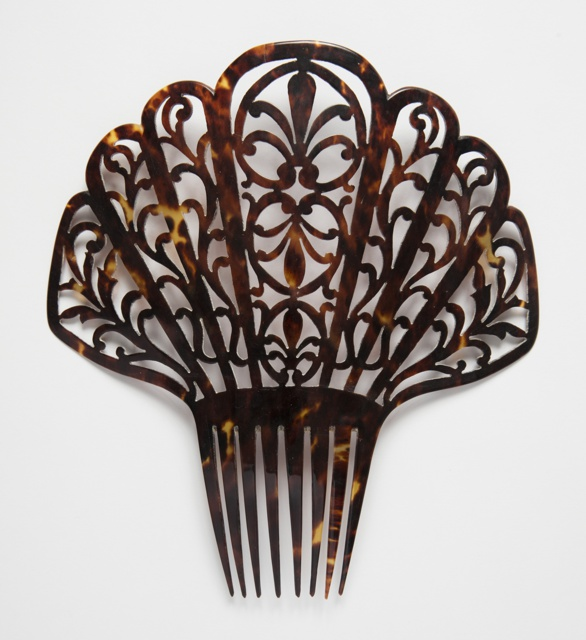 Large tortoiseshell comb with pierced stylized flower and vine motifs.