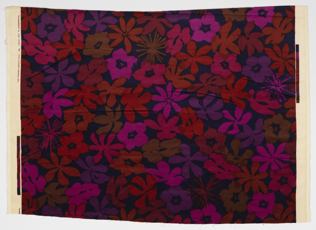 Textile with red, pink, purple, and maroon floral pattern on a dark background.