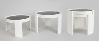 Group of four white cylindrical nesting tables of graduated size, each with three curved, broad panel legs and a flat circular reversible plastic top, black on one side, white on the other.