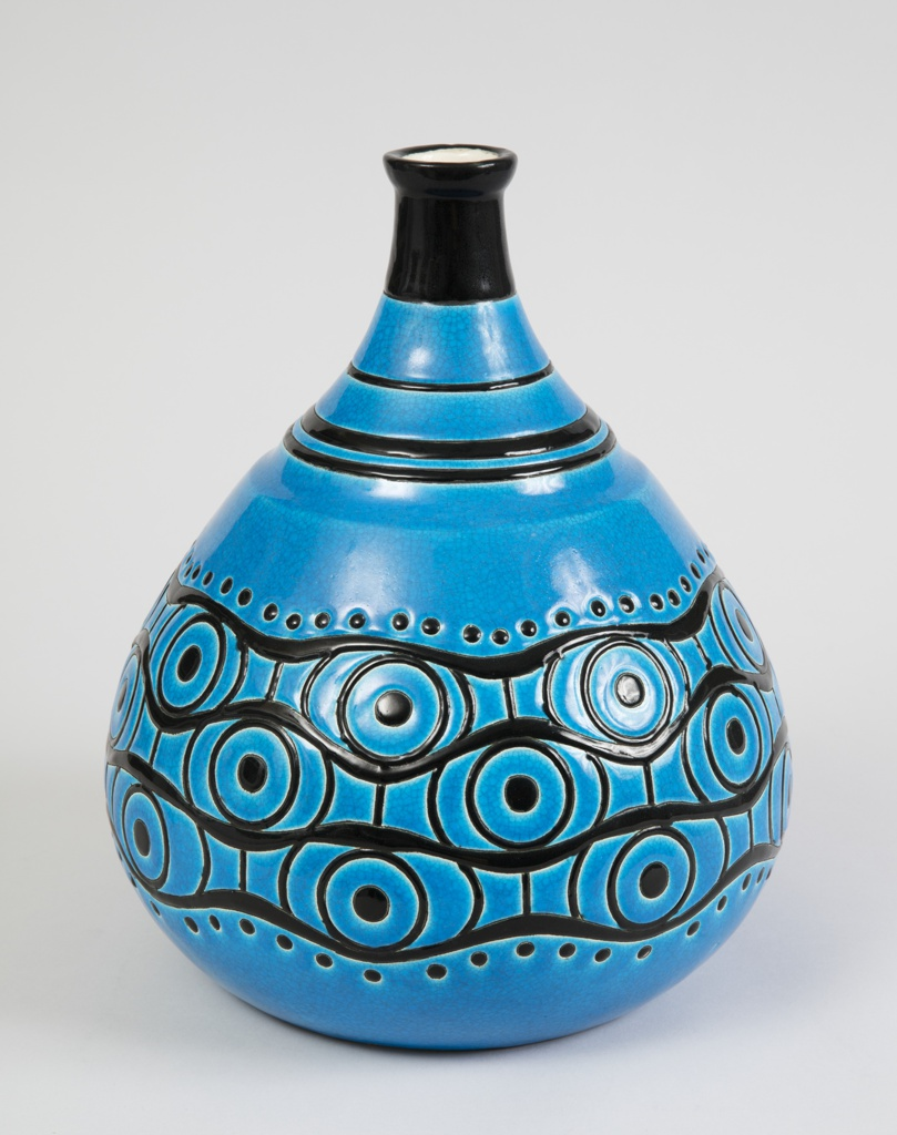 Tear-drop shaped blue vase with black banding at neck and border of swooping lines dots and spirals around body