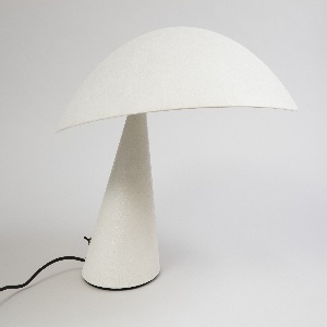 Lamp composed of broad, overhanging elipitcal shade attached at one side to angled conical base; swtich and black cord at rear of base.