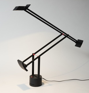 Black form consisting of a small rectilinear lamp housing with reflector supported by two pairs of counter-weighted adjustable arms set on a swivelling cylindrical base with cooling slots; red plastic stops on chrome bars set between arms; red plastic switch on top of base.