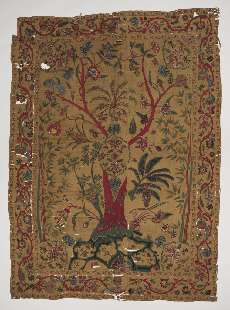 Bedcover embroidered in multicolored silk with a flowering tree in a field and floral vine border with birds. On a tobacco-brown ground.
