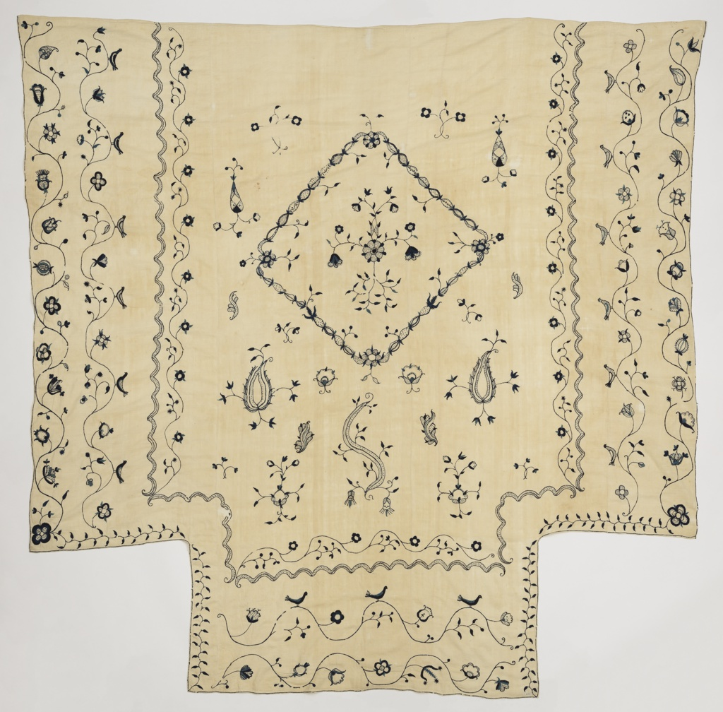 Bedcover in cream-colored cotton with crewel embroidery in blue wool. Diamond-shaped center design framing flower clusters; detached designs of flowers and foliage. Wide borders for sides, vine and birds, and a separate drop for the foot of the bed in the same design.