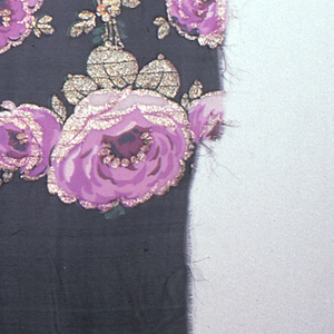 Sample in sheer solid black silk with a deep border design of pendant sprays of roses, printed in shades of violet with green leaves and brocaded with gold thread. Both selvedges present.