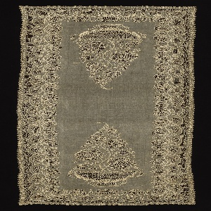Long rectangular whitework shawl with a bowl of flowers on each end surrounded a vine and flower border.
