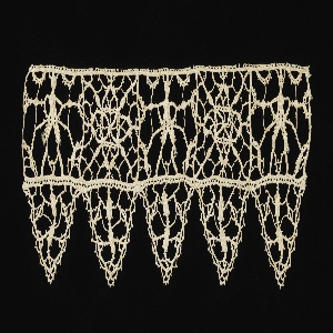 Border with geometric pattern of squares showing alternating human shapes and star motif. Edged with triangular pendants.