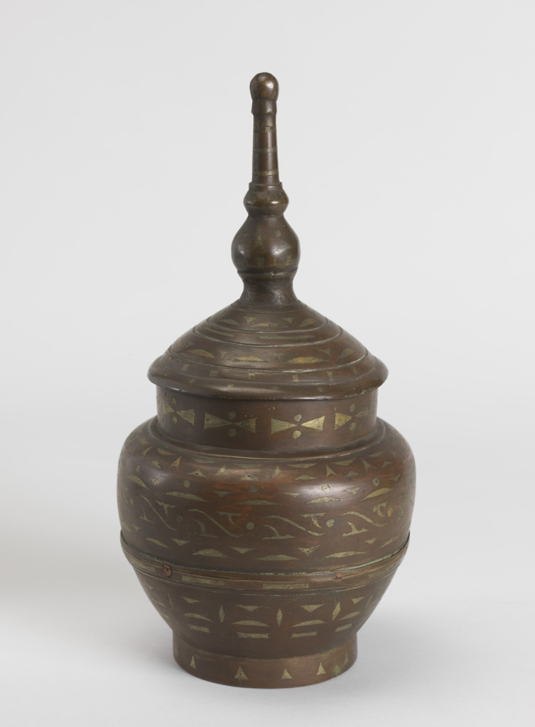 Footed jar (a) cast in two parts with encircling banding covering the joint.  Wide, short, straight neck.  Stepped lid (b) overhangs the neck, rises through curves to tall finial with two knobs topped by a ball.  The whole decorated with concentric bandings of inlaid white and brass-colored triangles, elipses, dots, S-curves, etc.