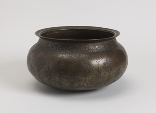 Bulbous bowl with wide lip, under which is a decorative band with text. Repeating pomegranate pattern on body.