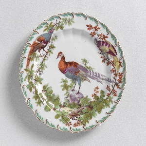 Scalloped edge with green feather motif. Fluted cavetto. At center, a tropical bird.