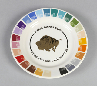 "White circular form with flat rim showing rectangular color samples with their corresponding color names; well with buffalo logo within circular surround: ""ONEIDA DINNERWARE / STANDARD ONGLAZE PALETTE."""