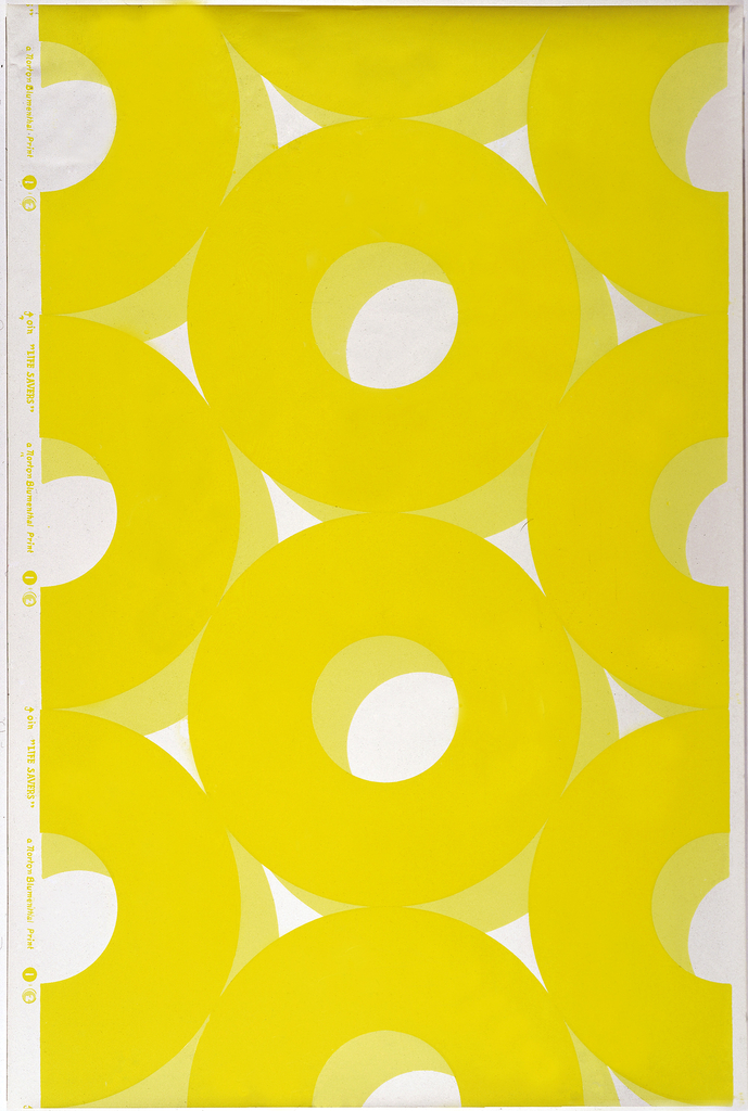 All-over pattern of large-scale yellow circles with lighter yellow shadow on white ground giving 3-D effect.