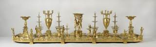 Centerpiece consisting of two urn-shaped freestanding gilt bronze candelabra, two bowls on pedestals, one large bowl supported by three female figures on pedestal, and eight gilt bronze and glass tiered stands, all arranged on five-section gilt-bronze and mirrored oval plateau; ten gilt bronze female figures in classical garb inserted at points in rim of plateau where sections are joined by architectonic pedestals. Figures typical of personages in the joyful chorus of a vintage celebration. Example of Thomire's production of classical themes of Greek origin in design. Companion objects for table: four short oval stands on rectangular bases, six short circular stands on square bases.  Glass 2-tiered dishes: (u and w); Urn-shaped candelabra bases (-hh and -jj); Four-arm candelabra tops (-ii and -kk); Bowls on pedestals: (-ll and -mm); Center piece with three figures: (-nn); Pedestals (-pp/-ww); Figures for pedestals (-f and -o):  Women wrapped in shawls ( -g and -n); Women with chalices ( -h and -f); Women with wreaths (- o and -i); Women with instruments ( -k and -j); Women with wheat sheafs (-m and -l). Companion objects: Oval stands (-x/ -aa); Circular stands: (-bb/-gg).