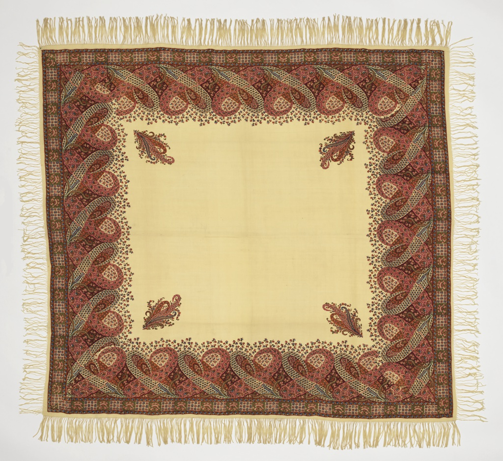 A square shawl with a border of cone motifs enclosing flowers and geometrical forms. Yellow outlined in dark red and blue. In each corner of the center square is a cone motif with sprays of flowers. Background is tan. Long fringe all around.