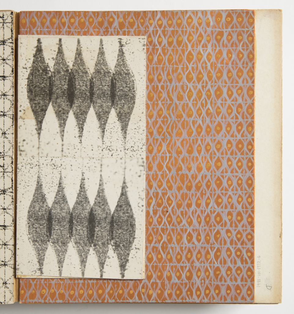 Design for plastic laminate. Vertical swatch comprised of two sheets; white ground speckled with gray. Two horizontal registers of five overlapping vertically elongated gray rhombi with curved sides and points above and below.