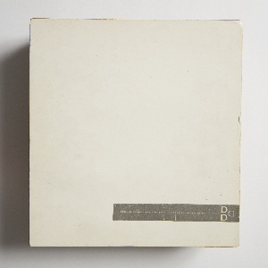 Accordion-style bound album of plastic laminate designs. Front cover consists of white cardboard panel with Donald Deskey Associates gray adhesive label affixed at lower right.