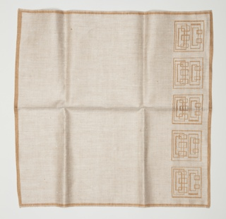 Linen damask napkins with a geometric design of interlocking squares along one edge, in light tawny brown.