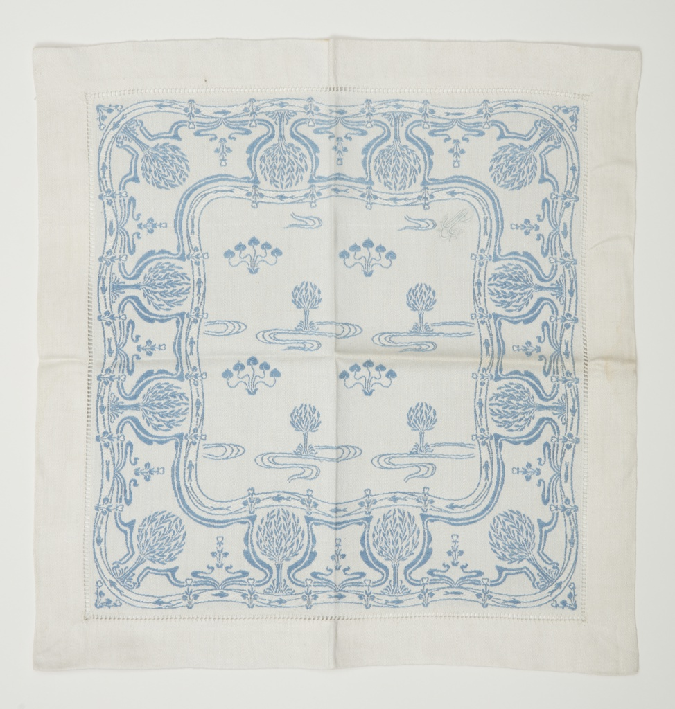 Art Nouveau napkin in blue and white has a deep border with a design of styled trees and flowers set within scrolling and sinuous lines. The central field has identical scaled-down trees and plants with spade-like leaves. Wispy lines encircle each tree. Central field and outer border are enclosed by a curvilinear frame that is filled with swimming fish.