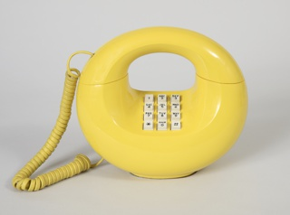 Phone with curved yellow plastic housing in a circle shape with a void between the handset and base. Base of the phone takes a half-circle shape with a flat bottom and white touch-tone keypad at center top. Phone handset forms the upper-half of the circular body and has a coiled yellow cord.