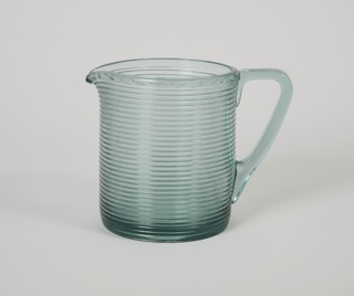 Pitcher of transparent ribbed smoky quartz body with handle; circular rim with spout.