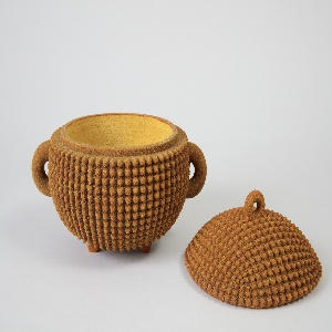 Ovular, footed vessel covered in a bumpy texture; semi-circular handle on each side; lid covered in same bumpy texture has a small circular handle on top; exterior is a deep, reddish brown, with an orange interior